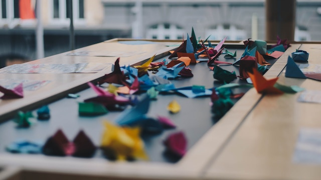three line tales, week 83: origami paper cranes on a table