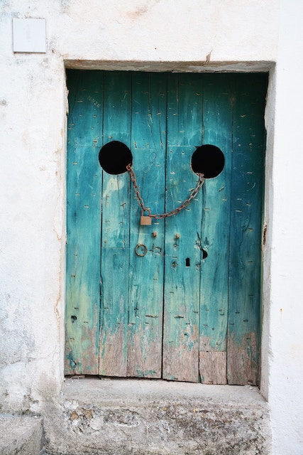 three line tales week 97: a blue wooden door with a face
