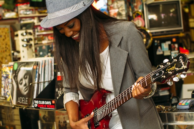 three line tales, week 147: a woman playing guitar in a shop
