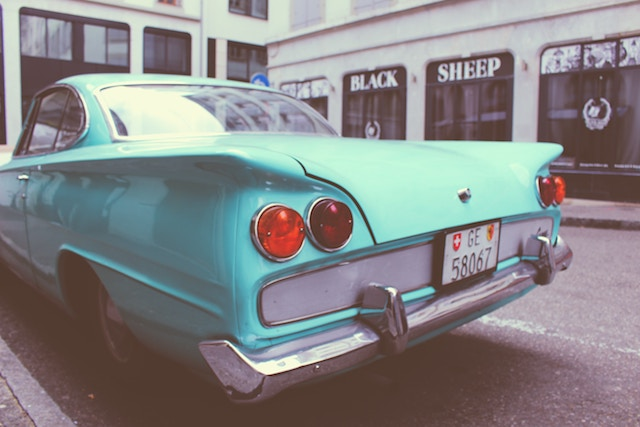 a turquoise car with fin tails