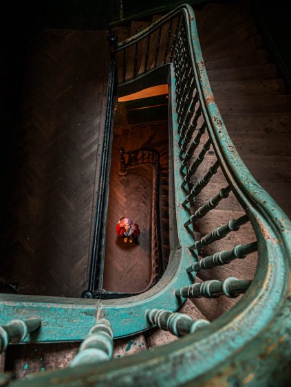 three line tales, week 190: an old winding staircase with a person standing at the bottom