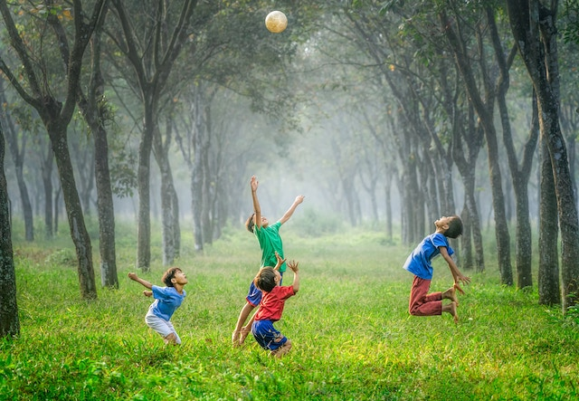 four boys playing football in a lush green meadow