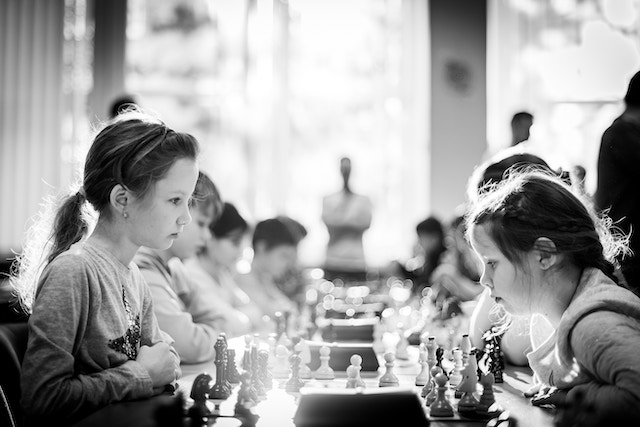 three line tales, week 206: children playing chess with a pair of girls in the foreground; chess friends