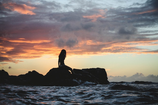three line tales, week 212: a mermaid sitting on a rock in the ocean during golden hour