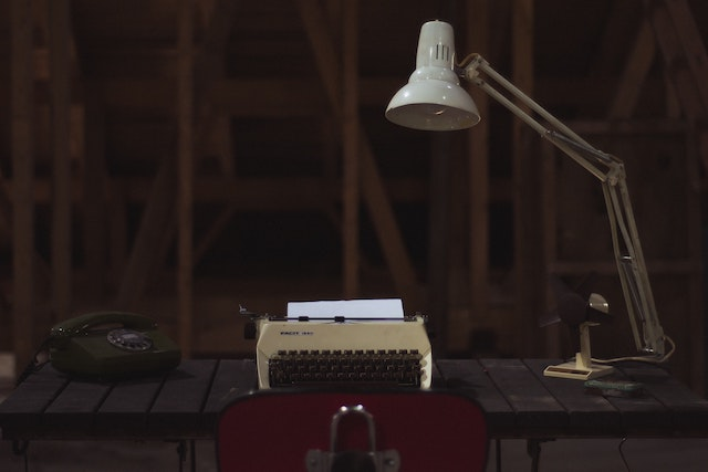 three line tales, week 213: an old school desk with lamp, rotary telephone and typewriter
