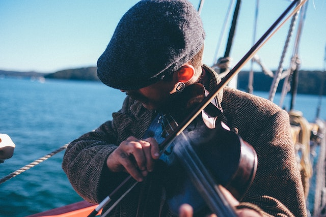three line tales 234: a man playing the fiddle on a boat