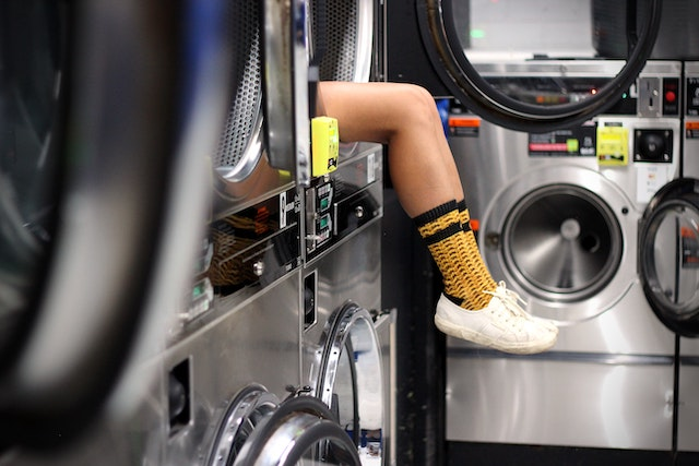 legs sticking out of a washing machine in a launderette
