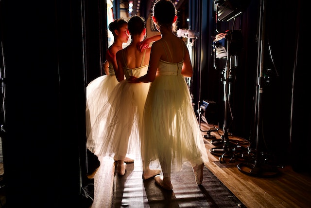 three ballerinas in white tutus backstage