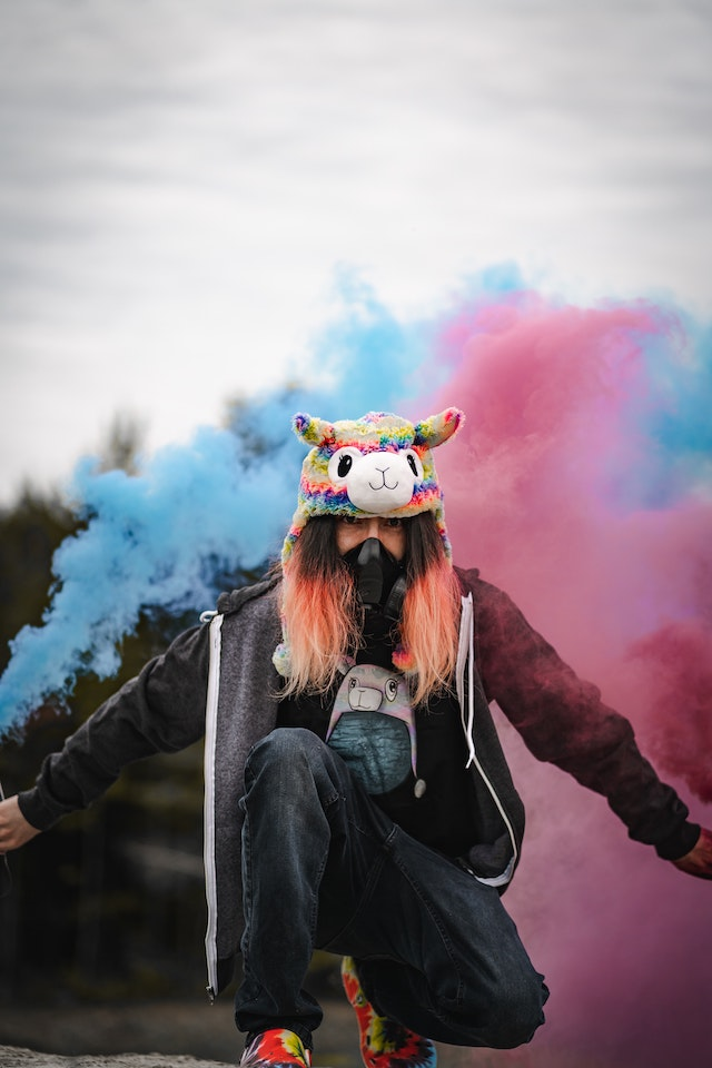 woman wearing a plush toy hat in front of blue and pink smoke