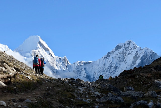two people on a mountain with the summit of Mount Everest in the background