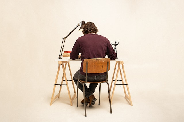three line tales, week 258: a man sitting at a desk with his back to the camera