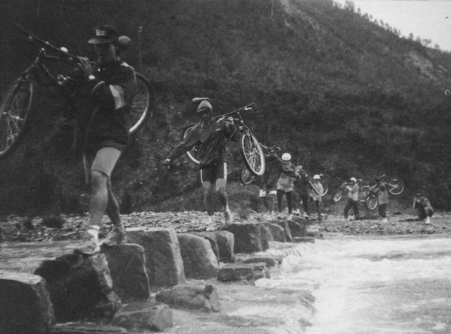 three line tales, week 259: cyclists carrying their bikes over a rocks in a river