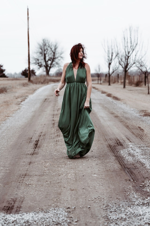 three line tales, week 265: a woman in a green ballgown walking down a dirt road barefoot
