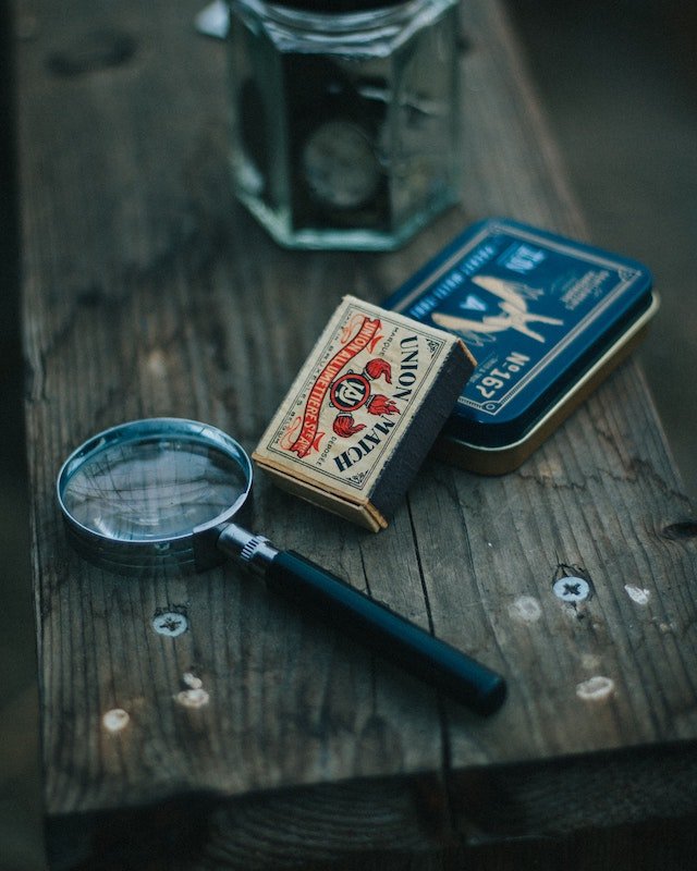 three line tales, week 268: a magnifying glass and a box of matches on a wooden surface