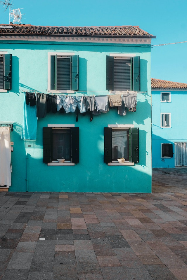 three line tales, week 275: blue washing in front of a turquoise house under a clear blue sky